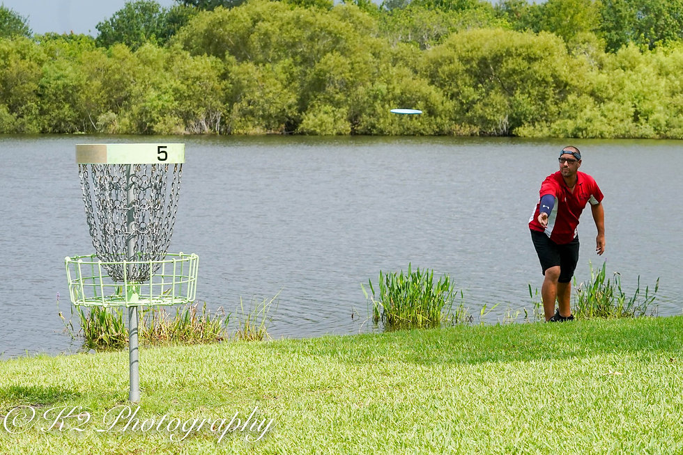 man playing disc golf next to lake