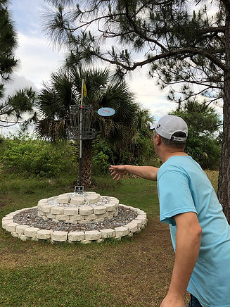 man throwing a disc a disc golf basket