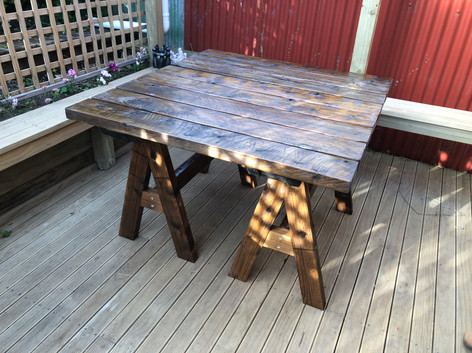 Table on movable trestle legs