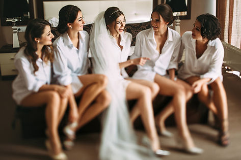 Bride in the center of her bridesmaid's laughing