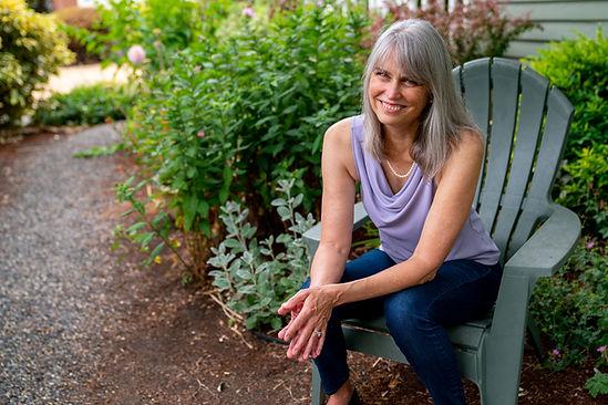 Sally sitting in her garden in a green lawn chair