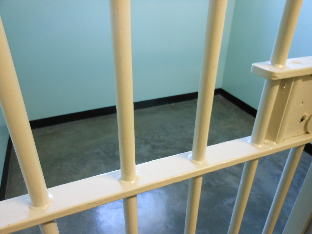 Photo of bars over a prison cell