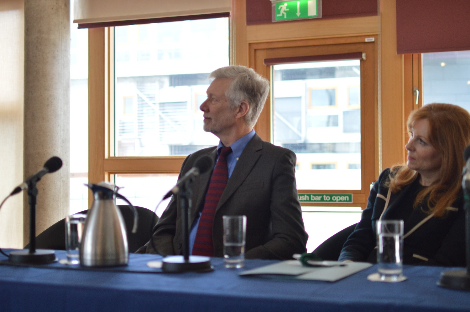 Keynote speakers Kevin Bales and Ash Denham MSP listen to a presentation.