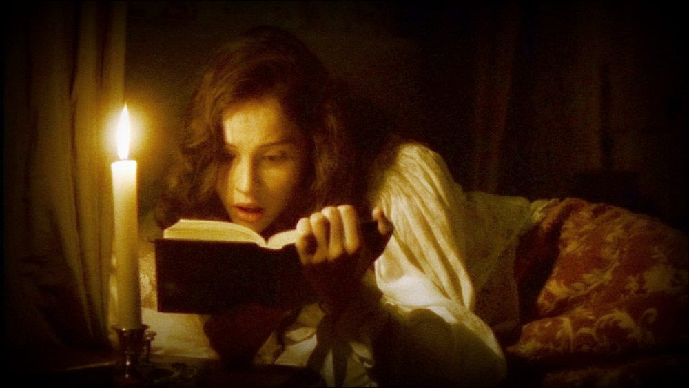 Felicity Jones as Catherine Morland reads a gothic novel by candlelight.