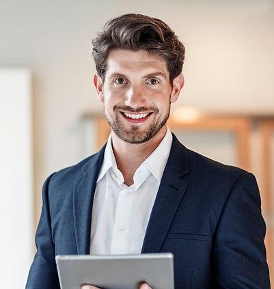 Zuversichtlich Geschäftsmann, der ein Tablet in der Hand hält und in die Kamer blickt.