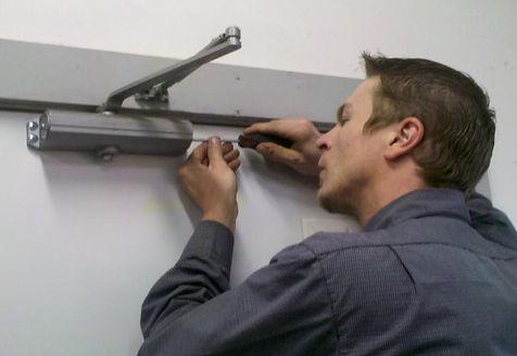 Technician adjusting door closure