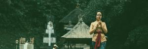 A woman holding incense near an altar.