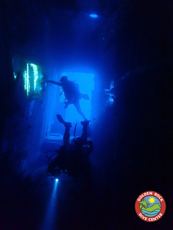 experienced scuba divers explore the wreck