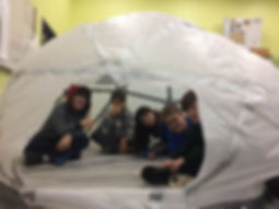 Five students peeking out of a bubble fort