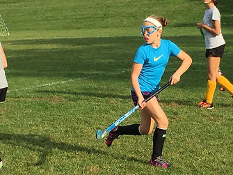 a girl running with a field hockey stick
