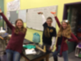 two girls and a boy with their hands in the air showing their science experiment