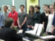 a group of chorus students singing standing up
