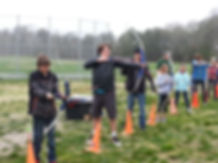 students in a line practicing archery