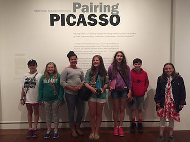 7 students lined up infront a Picasso wall