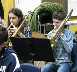 a girl and a boy playing the trombone