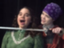 student putting a sword on another student in a play