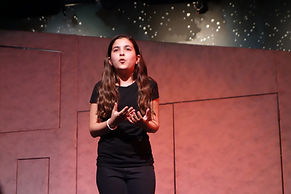 A youth actress sings a melody in Alison Kalmus Theater