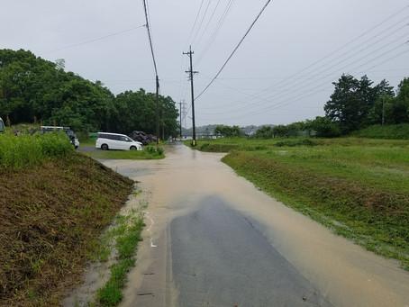 事務所の駐車場前の道路が水たまりに