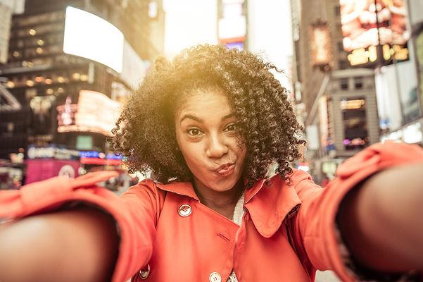 Young american woman taking selfie in Ne