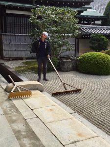 Gardener raking gravel