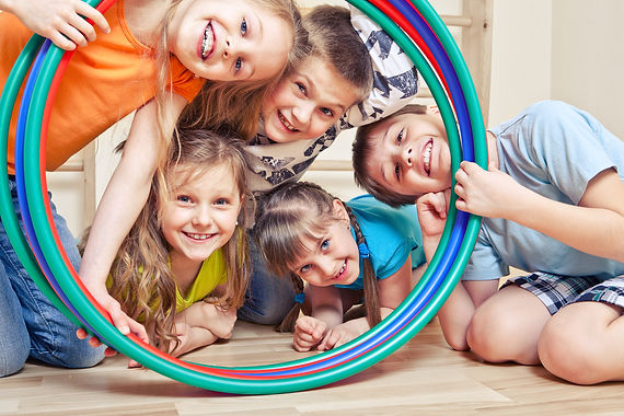 Five cheerful kids looking through hula hoops.jpg