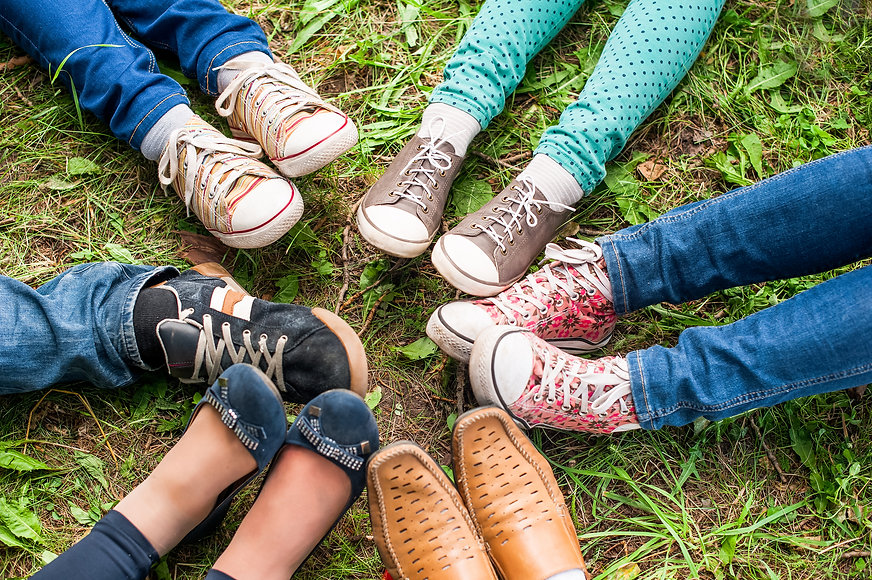 A Group Of Friends Sitting On The Green Grass Make Foot Circle With Their Legs Adn Different Shoes..