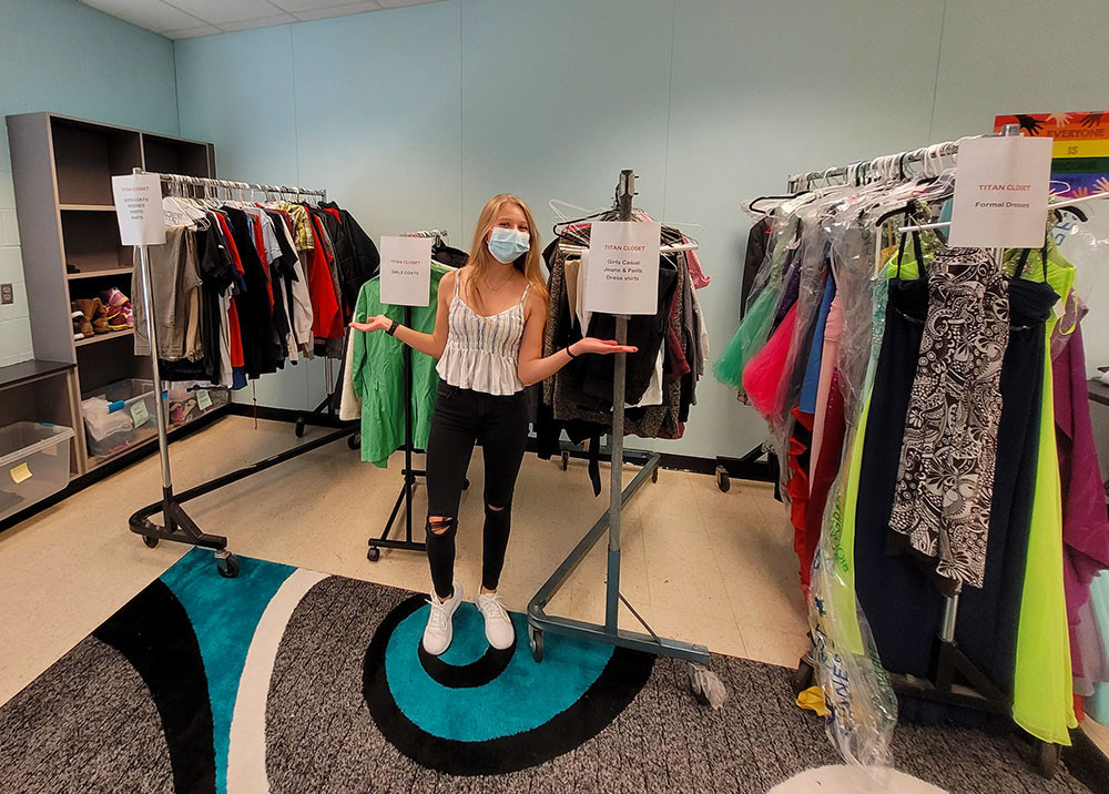 Student standing in front of donated clothes items for Titan Closet