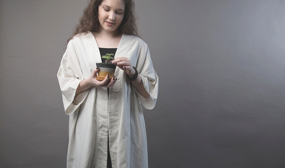 Na foto, a modelo veste kimono-robe na cor cru sobre uma blusa preta. Ela sorri e olha para o vasinho de suculenta que segura na mão, Fundo da foto cinza, liso.