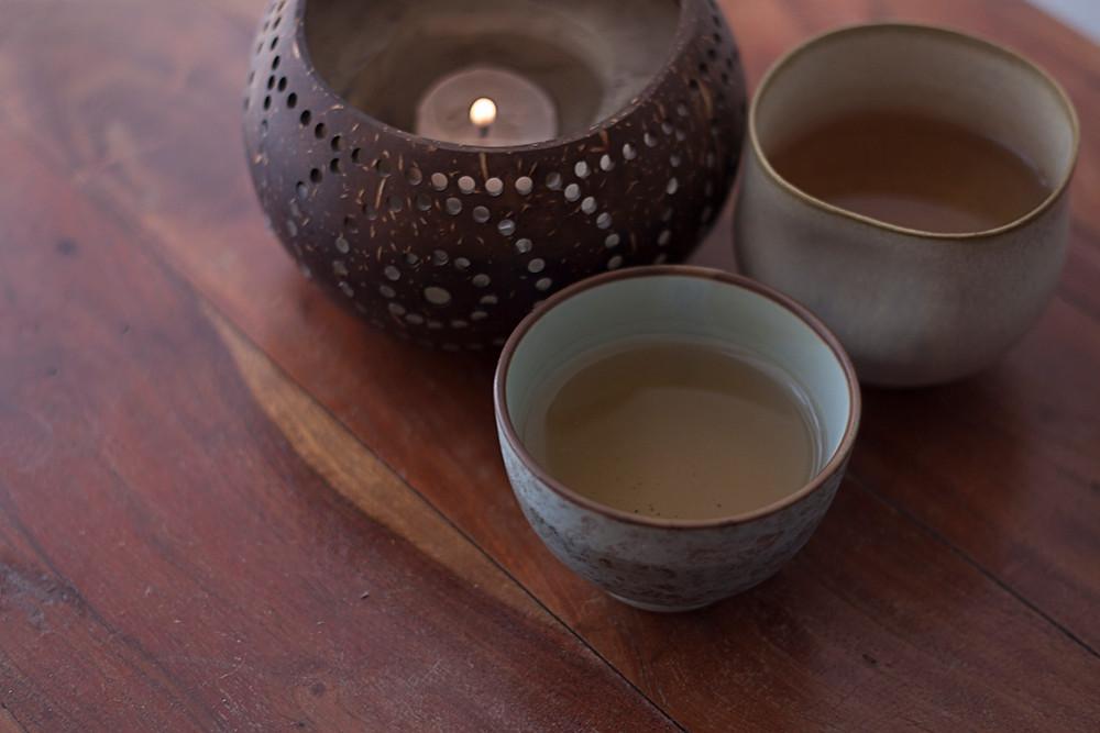 A foto mostra uma cumbuca de madeira perfurada com uma pequena vela acesa dentro. Ao lado, um bowl rústico de cerâmica verde com chá dentro. Atrás, parte de outra cerâmica. Estão sobre uma superfície de madeira escura com visual rústico