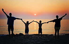 Image of a family holding hands and raising them