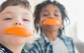 image of children with orange slices in their mouths
