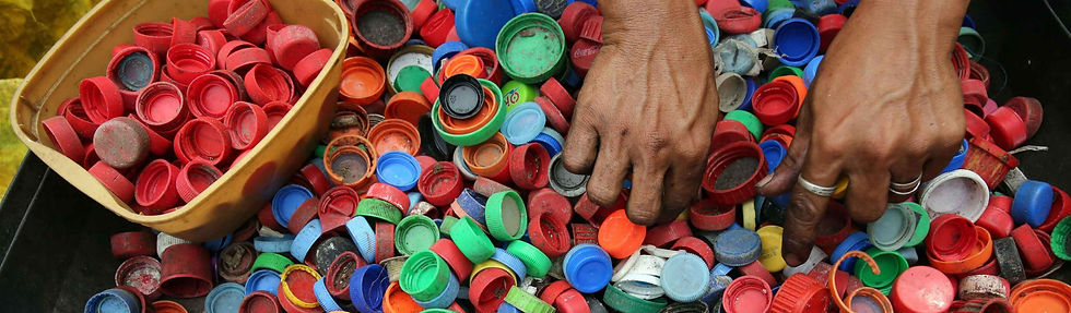 Image of someone putting their hands into a bucket full of plastic bottle lids