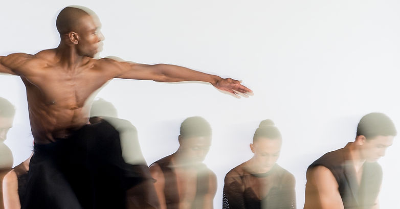 Blurry dancers. Male dancer in motion in the front with arms out to the side