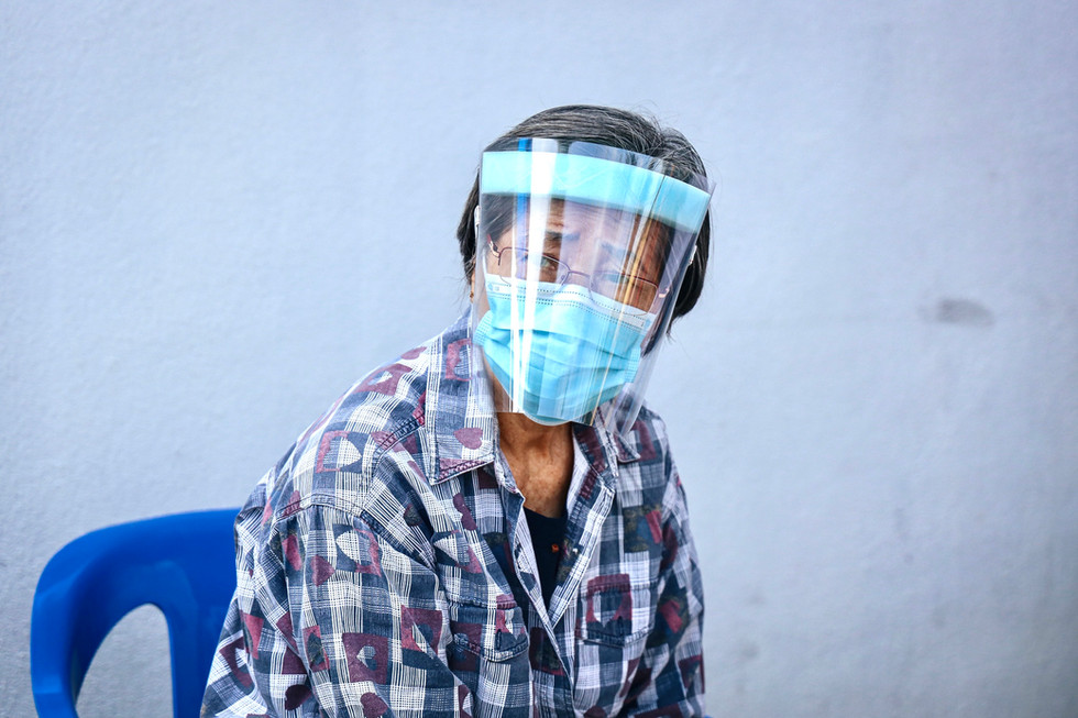 A elderly patient anxiously waiting for her name to be call in a public medical centre proceed for treatment.