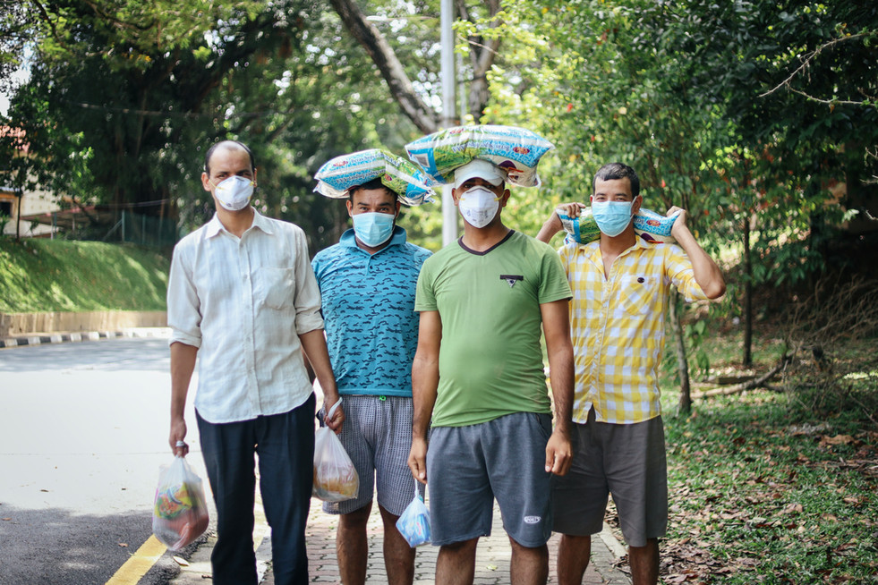A group of immigrants post for a photo, as they head out by foot to get their daily necessities. The government will declare later that evening that the nation wide Movement Control Order (MCO) will be extended to12 May 2020 in Malaysia.