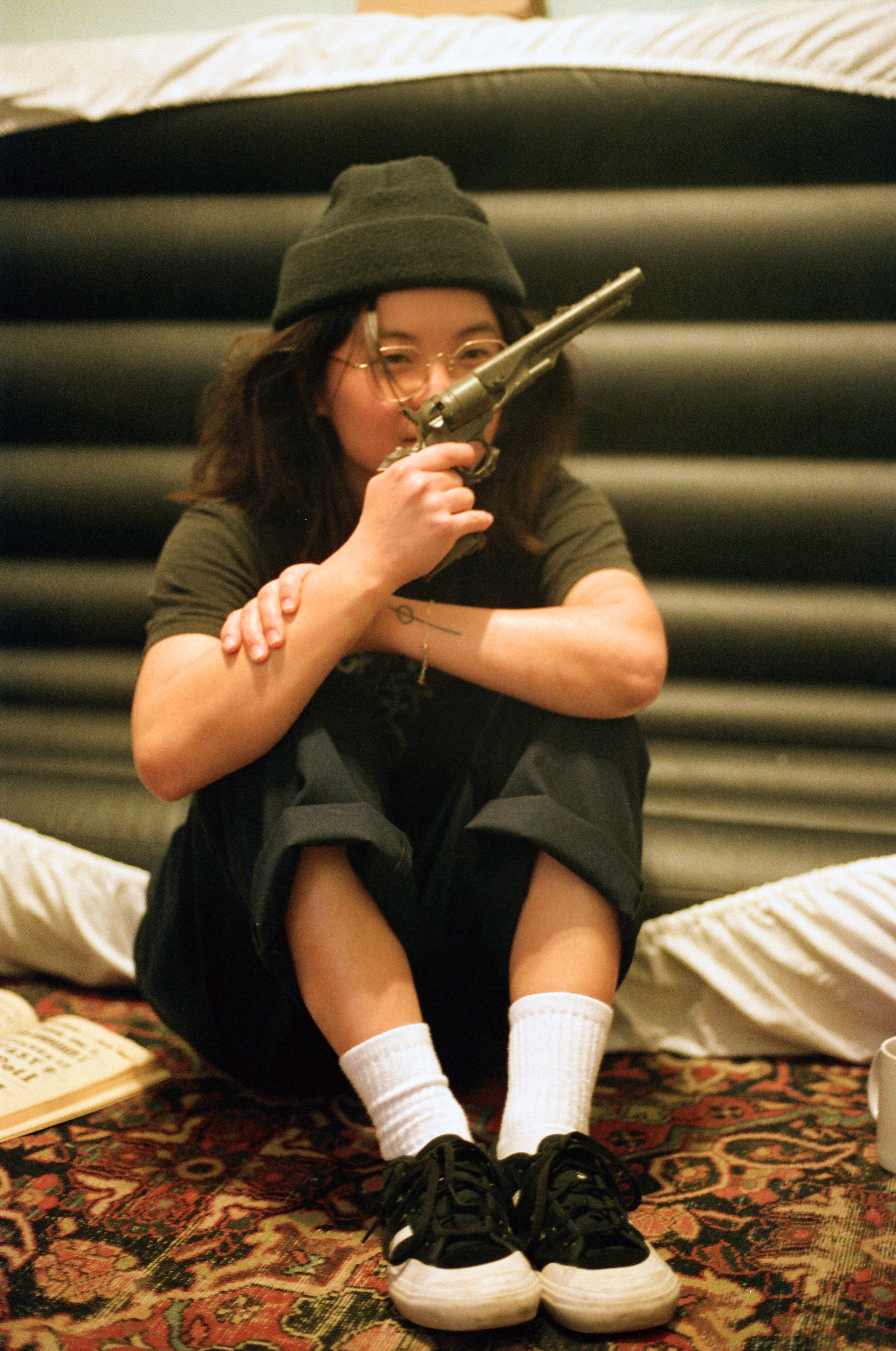 film portrait photograph of woman holding fake gun in front of upright air mattress