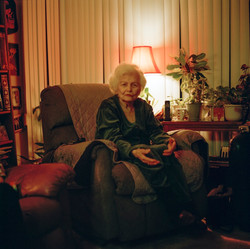 holocaust survivor talks at camera while sitting on chair in her home
