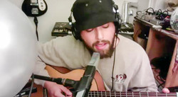 Photograph of Musician Nick Hakim singing and playing guitar over zoom for MoMA PS1