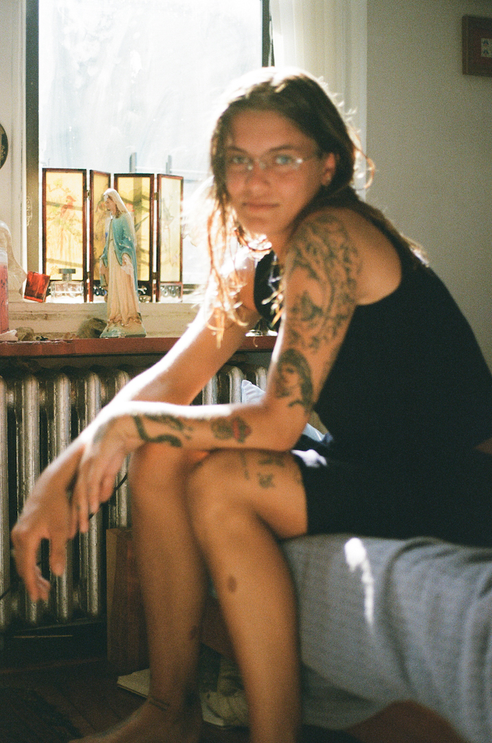 contemporary fine art film photograph of blurry tattooed woman in front of Virgin Mary nyc