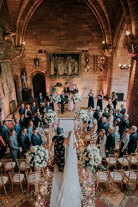 Peckforton Castle wedding flowers and ceremony. Wedding florist in Cheshire. Tall trumpet vases and venue decoration in Cheshire, Chester, Liverpool, Manchester and Lancashire. Florist in Warrington