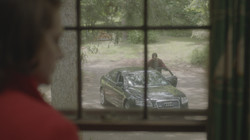 OTS shot of Barbara from the window on Bobby at the car