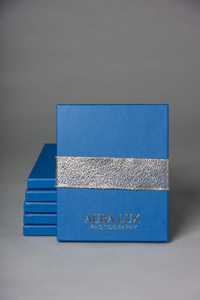 Blue photo box with Aura Lux Photography stamped on it and a gold ribbon in Winter Garden FL. Print packaging.