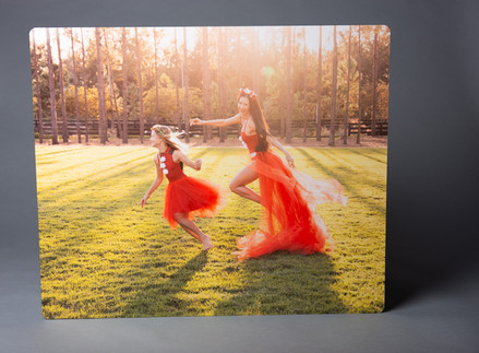 A metal print of a dark haired woman in a red Christmas ballerina costume chasing her blonde daughter in a red Christmas tutu with sun flare in Winter Garden FL. Aura Lux Photography. Family photography