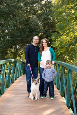 Family standing on bridge with dog