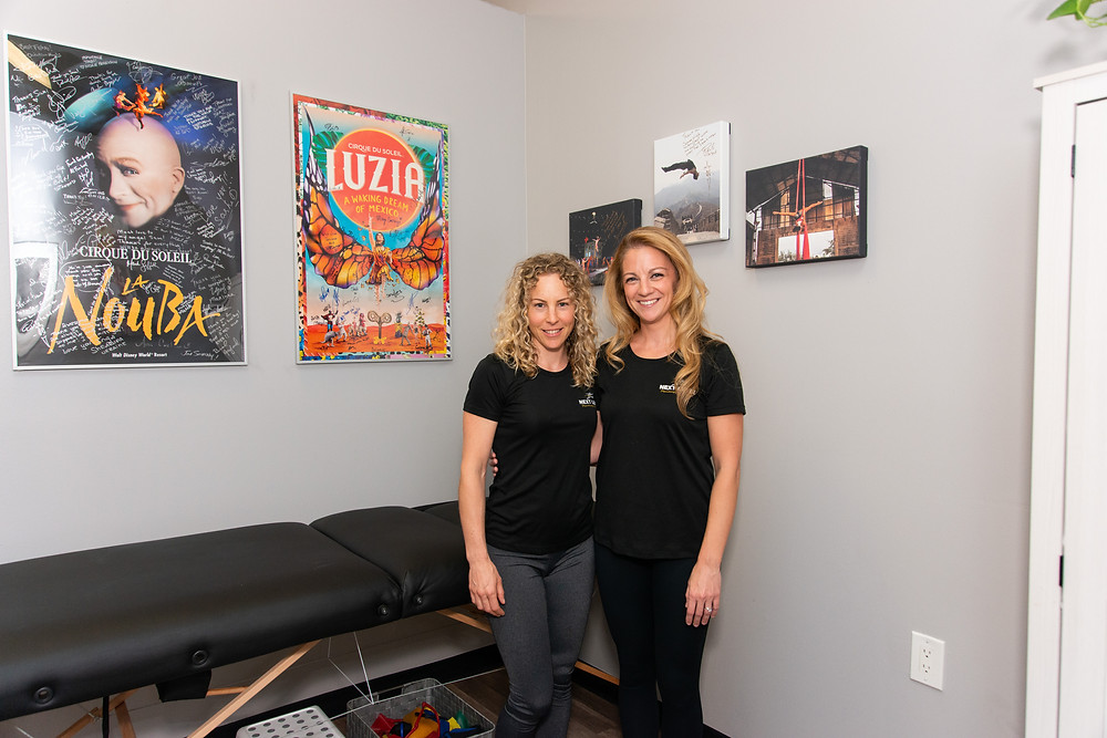 Nicole Ferguson and Sam Oft in Next Level Physiotherapy office with Cirque du Soleil posters.