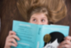 Dark blonde girl with brown eyes reading Wonder book while laying on floor.