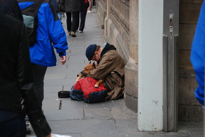 A homeless man sitting hunched over, clutching his dog, on the streets of Edinburgh