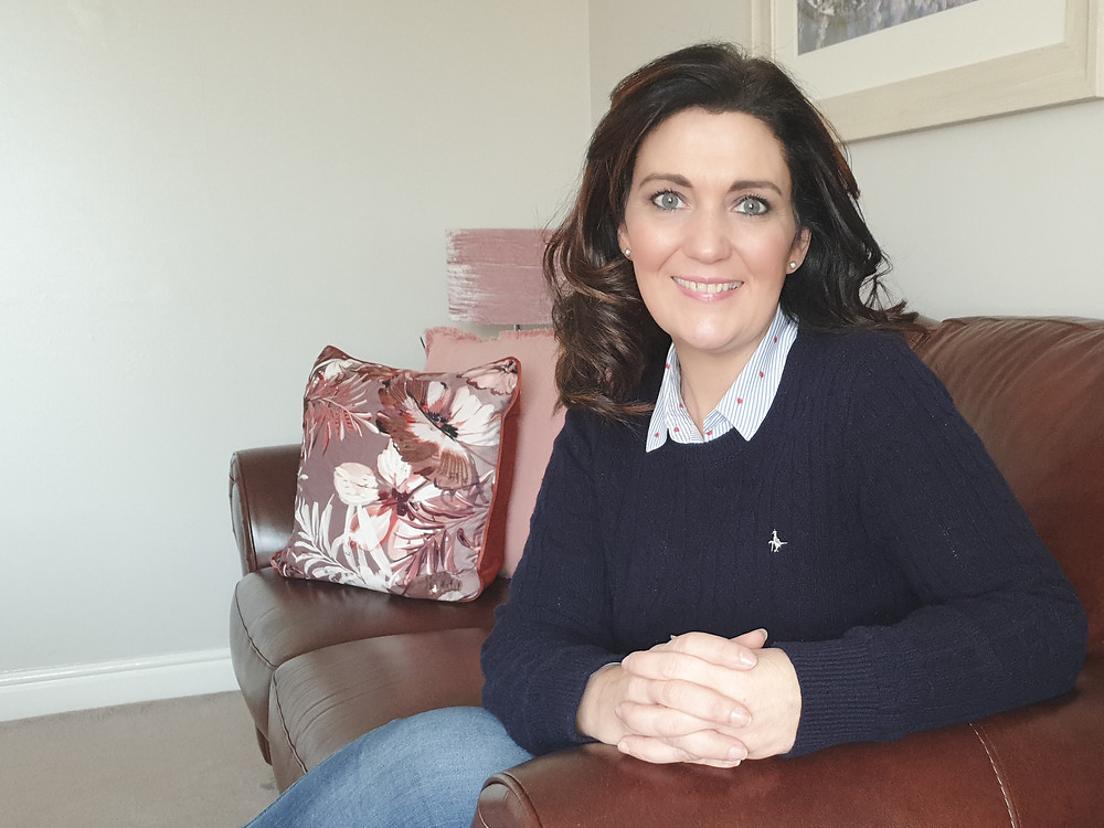 A smiling brunette businesswoman sits on a sofa. Online photography. Online photoshoot. Online photographer. Online personal brand photography. Personal brand. Personal brand photoshoot