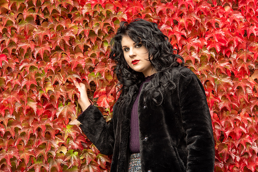 A black haired woman stands in front of a red ivy covered wall. Travel blog. Travel photographer. Roadtrip4charity. Commercial photographer. Wedding photographer. Newborn photographer. Portrait photographer. Business photographer. Family photoshoots. Family photography. Business photographer. Road trip. Elton Cilliers. Portraits in the Park. Creative. Creativity. Marketing. Brand. Personal brand.