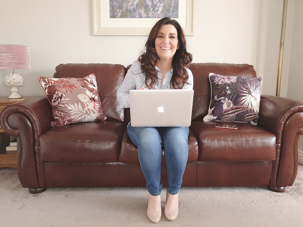 A smiling brunette businesswoman sitting on a sofa with a laptop. Online photography. Online photoshoot. Online photographer. Online personal brand photography. Personal brand. Personal brand photoshoot